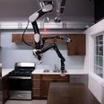 A Toyota robot suspended from the ceiling gets to work wiping a counter.